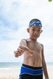 Garçon et bernard l'ermite espiègles sur la plage. Image stock