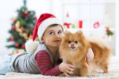 Garçon et chien d'enfant appréciant dans la caresse dans le temps de Noël Image stock