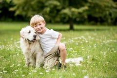 Garçon et chien heureux comme amis Photo stock