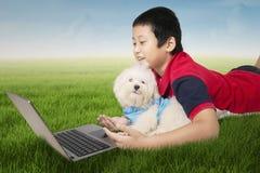 Garçon et chien utilisant l'ordinateur portable au champ Photos libres de droits