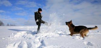 Garçon et crabot jouant dans la neige Photographie stock