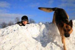 Garçon et crabot jouant dans la neige Images stock