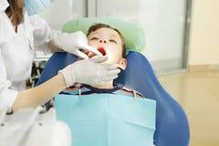 Garçon et dentiste pendant une procédure dentaire Photographie stock libre de droits