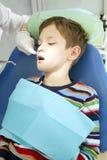 Garçon et dentiste pendant une procédure dentaire Photos stock
