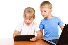 Garçon et fille à l'aide de la garniture et de l'ordinateur portatif digitaux images libres de droits