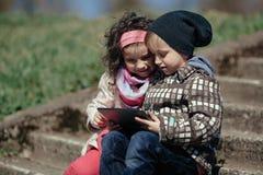 Garçon et fille à l'aide du comprimé Photos libres de droits