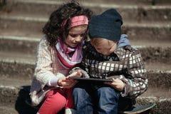 Garçon et fille à l'aide du comprimé Image libre de droits