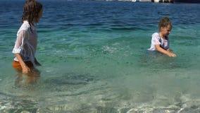 Garçon et fille éclaboussant l'eau, se tenant à la taille en mer Les vêtements des enfants obtiennent enfance humide et heureux banque de vidéos