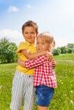 Garçon et fille étreignant dans le domaine vert Photos stock