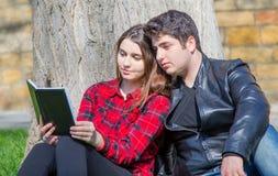 Garçon et fille affichant un livre Photos stock