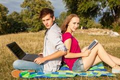 Garçon et fille apprenant en parc avec l'ordinateur portable et le comprimé Photos libres de droits
