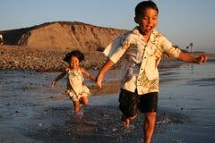 Garçon et fille asiatiques heureux sur la plage Photographie stock