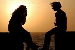 Garçon et fille au coucher du soleil Photographie stock libre de droits