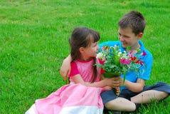 Garçon et fille avec des fleurs Image libre de droits