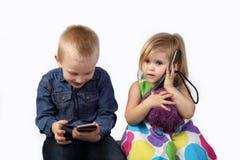 Garçon et fille avec des téléphones portables sur le gris Images libres de droits