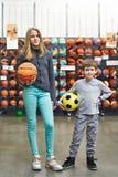 Garçon et fille avec du ballon de football et basket-ball dans le magasin Image libre de droits