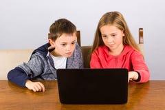 Garçon et fille avec l'ordinateur portatif Images libres de droits