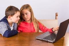 Garçon et fille avec l'ordinateur portatif Photo stock