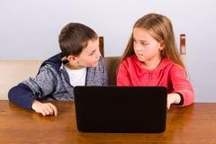 Garçon et fille avec l'ordinateur portatif Photos libres de droits