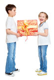 Garçon et fille avec le boîte-cadeau rouge et l'arc d'or - concept d'objet de vacances d'isolement Photos libres de droits