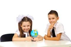 Garçon et fille avec le globe Image libre de droits