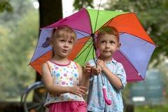 Garçon et fille avec le parapluie Photos stock