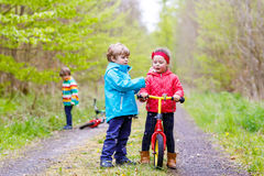 Garçon et fille avec les bicyclettes et le pissenlit de soufflement Photographie stock