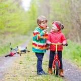 Garçon et fille avec les bicyclettes et le pissenlit de soufflement Images stock