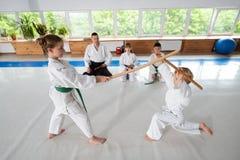 Garçon et fille ayant le combat d'aikido utilisant le jo photographie stock