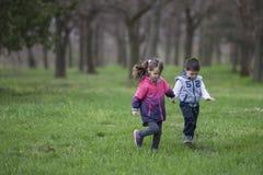 Garçon et fille courant en parc photos stock