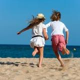 Garçon et fille courant vers la mer. Photographie stock