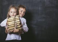 Garçon et fille d'école primaire dans la salle de classe avec des livres Photo libre de droits