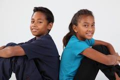 Garçon et fille d'amitié d'école s'asseyant ensemble Photos libres de droits