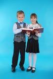Garçon et fille dans l'uniforme scolaire lisant un livre Photo libre de droits
