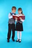 Garçon et fille dans l'uniforme scolaire lisant un livre Image libre de droits