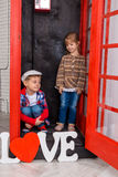 Garçon et fille dans la cabine de téléphone Images stock