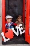 Garçon et fille dans la cabine de téléphone Photographie stock libre de droits