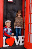Garçon et fille dans la cabine de téléphone Photo stock