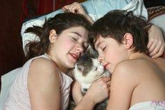 Garçon et fille dans le lit avec la fin de chat vers le haut du portrait Photos libres de droits