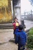 Garçon et fille dans le manteau jouant près de la rue dans Cat Cat Village photo libre de droits