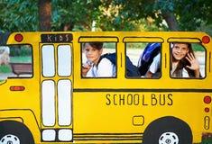 Garçon et fille dans le petit autobus scolaire image stock