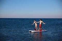 Garçon et fille de bonheur tenant des mains sur la natation de ressac de petite gorgée à l'océan Mode de vie de concept, sport, a Photo libre de droits