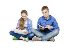 Garçon et fille de l'adolescence d'âge avec le comprimé et le carnet Image libre de droits