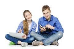 Garçon et fille de l'adolescence d'âge avec le comprimé et le carnet Photographie stock