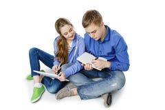 Garçon et fille de l'adolescence d'âge avec le comprimé et le carnet Photographie stock libre de droits