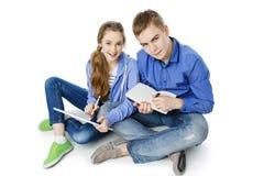 Garçon et fille de l'adolescence d'âge avec le comprimé et le carnet Photos stock