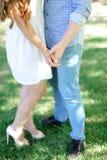 Garçon et fille de plan rapproché tenant des mains à l'arrière-plan d'herbe Images libres de droits