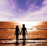Garçon et fille de silhouette sur la mer Images libres de droits