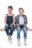 Garçon et fille de sourire à l'aide des dispositifs numériques tout en se reposant sur le banc, Photographie stock