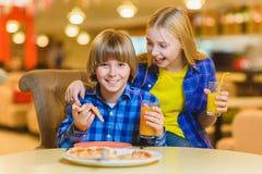 Garçon et fille de sourire mangeant de la pizza ou buvant du jus d'intérieur Photographie stock